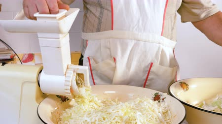 gıda maddesi : A male chef is chopping cabbage in a kitchen electric grinder. Slow motion.