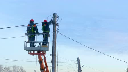 emel : Electricians in uniform repair power lines, standing on the bucket. Winter day. Cold weather. In the background is a blue cloudy sky.