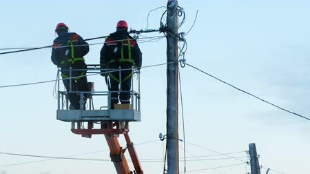 гидравлический : Electricians in uniform repair power lines, standing on the bucket. Winter day. Cold weather. In the background is a blue cloudy sky.