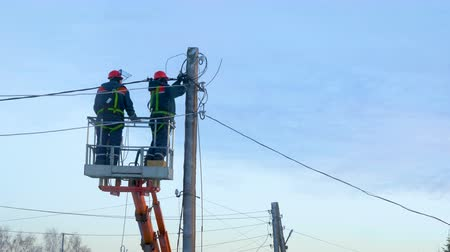 schlange stehen : Electricians in uniform repair power lines, standing on the bucket. Winter day. Cold weather. In the background is a blue cloudy sky.