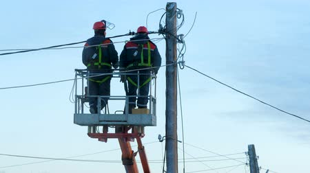hydraulické : Electricians in uniform repair power lines, standing on the bucket. Winter day. Cold weather. In the background is a blue cloudy sky.