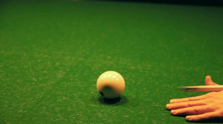 хит : A man prepares to hit the cue ball. A hand with a cue on a green background of a billiard table. Стоковые видеозаписи