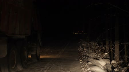 télen : A truck carrying ore rides along a forest snowy road in the winter season. Night time. View from the front window of the car. Stock mozgókép