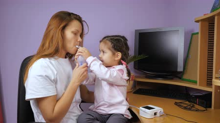 compressor : Mom teaches her little daughter to use a nebulizer. A girl sits on her lap and smiles.