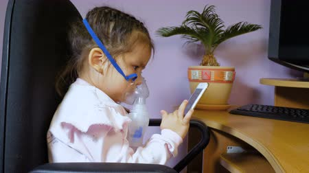 dýchání : A pretty little girl sits in a chair at the computer desk, is treated with a nebulizer and uses a mobile phone. Dostupné videozáznamy