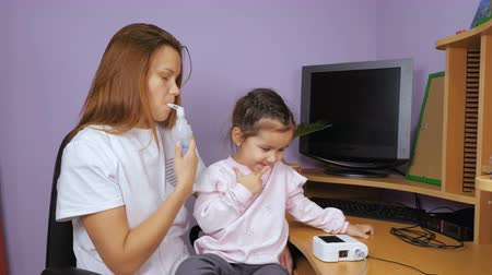 zabránit : Mom teaches her little daughter to use a nebulizer. A girl sits on her lap and smiles.