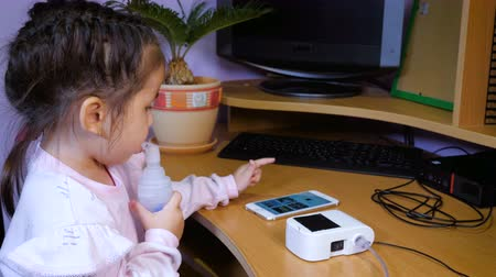 compressor : A pretty little girl sits in a chair at the computer desk, is treated with a nebulizer and uses a mobile phone. Stock Footage