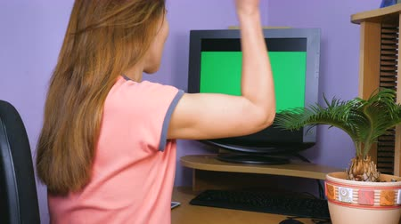 jóváhagyott : A young woman sits at a computer desk, looks at the monitor, rejoices and claps her hands. Stock mozgókép