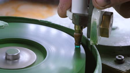 drahokamy : An gemstone cutter polishes a emerald on a faceting machine with chromium oxide in a cutting and polishing workshop. Dostupné videozáznamy