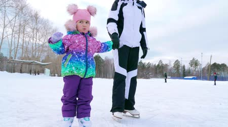 лед : Mom and her little cute daughter are learning to skate on the rink. Winter time. Slow motion.
