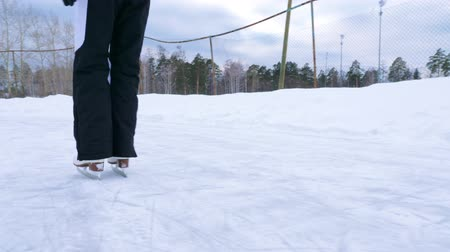 ice skating : A young woman is skating on an old outdoor skating rink. Winter time. Slow motion. Stock Footage