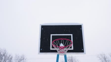 basketbalveld : Basketball ball flies into the basket in the winter. Its snowing outside. Stockvideo