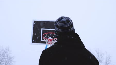 throws : The teenager throws the ball in the basketball hoop in the winter. View from the back. Its snowing outside.