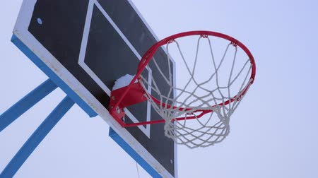 enferrujado : Basketball ball flies into the basket in the winter. Its snowing outside. Stock Footage
