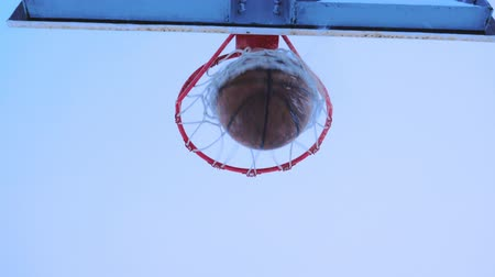 abroncs : Basketball ball flies into the basket in the winter. Its snowing outside. Stock mozgókép