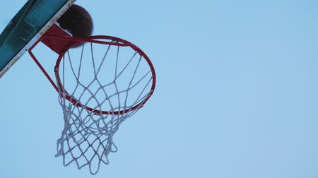 temperatura : Basketball ball flies into the basket in the winter. Its snowing outside. Stock Footage