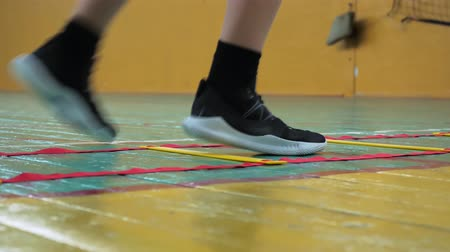 high school : Basketball training. Teens train in the school old sports hall. Coordination ladder exercises.