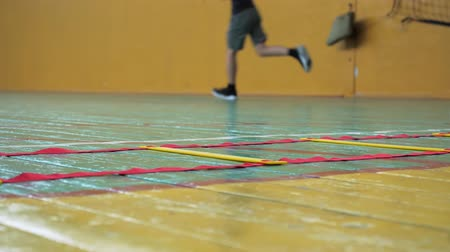 Basketball training. Teens train in the school old sports hall. Coordination ladder exercises.