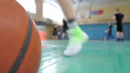 старшей школе : Basketball training. Teens train in the school old sports hall, throw the ball in the basket and run with the ball.