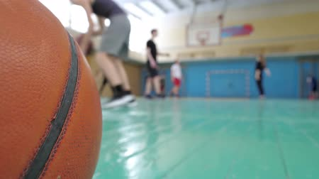 Basketball training. Teens train in the school old sports hall, throw the ball in the basket and run with the ball.