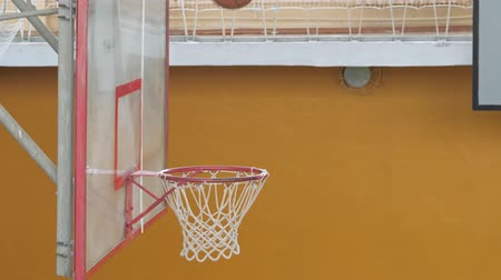 Basketball ball flies into the basket in the old sports hall. Slow motion. Wideo