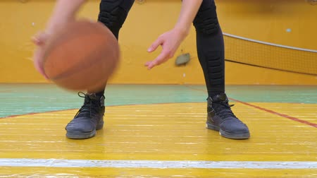 Basketball training. Teens train in the school old sports hall. Teenager dribbling the ball very quickly through and around his legs. Wideo