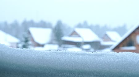 View from the snow-covered window on the village houses and the forest. Its snowing outside. Sliding video.