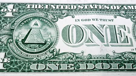 Sliding video of a one US dollar bill note, showing ONE text and image of the pyramid and the eagle. Macro shot. Close up.