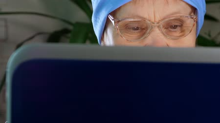An elderly woman with glasses uses a laptop at home. Close up.