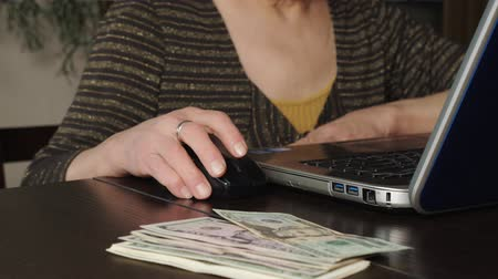 An older woman uses a laptop to make money online. Mouse in hand. On the table are dollars. Close up.