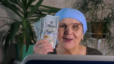 An elderly woman uses a laptop to make money on the Internet, shakes dollars in her hands, smiles and rejoices.