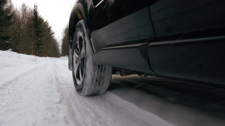 The car moves on a snowy forest road. Winter season. Car wheel close view.