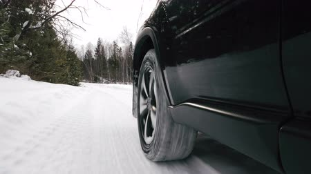 bétula : The car moves on a snowy forest road. Winter season. Car wheel close view.