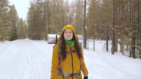 Girl tourist in orange winter clothes walking along a winter forest road with a backpack on her shoulders. Slow motion. Stock Footage