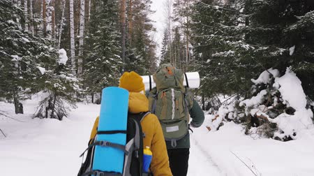 A young man and a girl are walking along a winter forest path with backpacks on their shoulders. Slow motion. Wideo