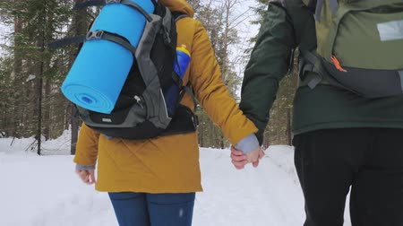 Tourists, a young man and a girl, walk along the winter forest path holding hands. Slow motion.