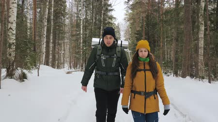 A young man and a girl are walking along a winter forest path with backpacks on their shoulders. Slow motion. Stock Footage