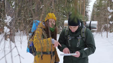 Two tourists with backpacks, a young man and a girl, in a winter snow-covered forest look at a paper map. Slow motion.