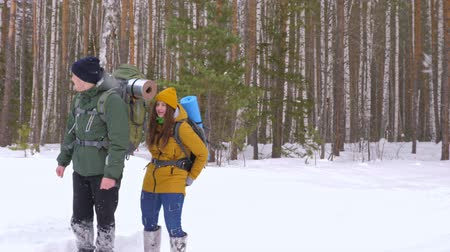 Funny video. A young man and a girl are walking along a winter forest path with backpacks on their shoulders. Slow motion. Wideo