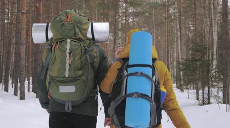 wooden path : Tourists, a young man and a girl, are walking along a winter forest path with backpacks on their shoulders and waving hands behind them. Slow motion.