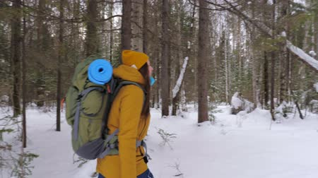 Girl tourist in orange winter clothes walking along a winter forest path with a backpack on her shoulders. Slow motion.
