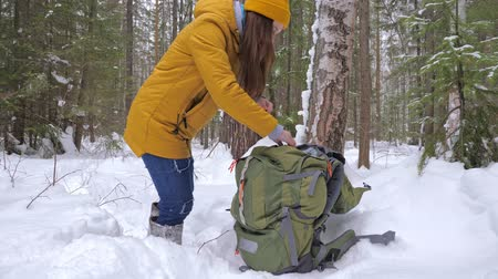 banka : Girl tourist in the winter snow-covered forest gets a vaccum flask with tea from a backpack. Slow motion.