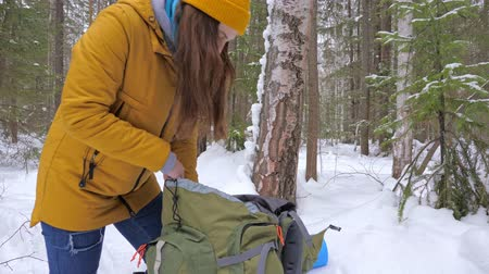 kap : Girl tourist in the winter snow-covered forest gets a vaccum flask with tea from a backpack. Slow motion.