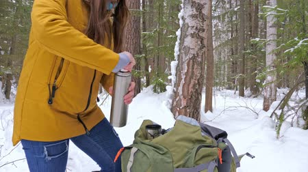 Girl tourist in the winter snow-covered forest gets a vaccum flask with tea from a backpack. Slow motion.