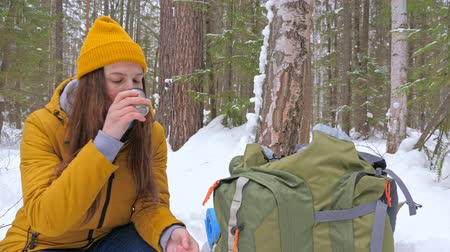 enjoys : Girl tourist in the winter snow-covered forest drinking tea from a vaccum flask next to a backpack. Slow motion. Stock Footage