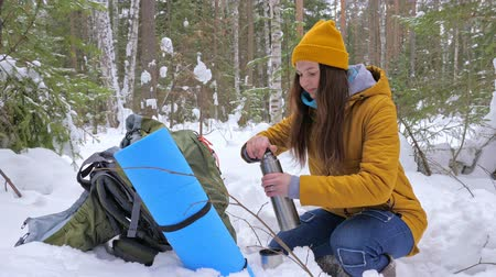 banka : Girl tourist in the winter snow-covered forest drinking tea from vaccum flask next to a backpack. Slow motion. Dostupné videozáznamy