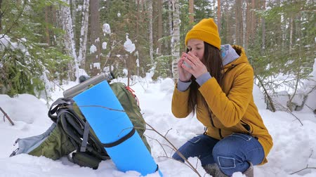 Girl tourist in the winter snow-covered forest drinking tea from a vaccum flask next to a backpack. Slow motion. Wideo