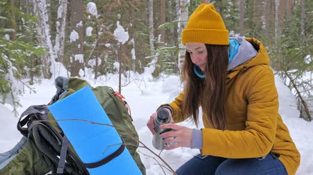 Girl tourist in the winter snow-covered forest drinking tea from a vaccum flask next to a backpack. Slow motion. Stock Footage