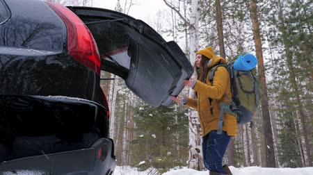 A girl tourist after a walk through the winter forest puts her backpack in the car trunk. It is snowing outside. Slow motion. Wideo