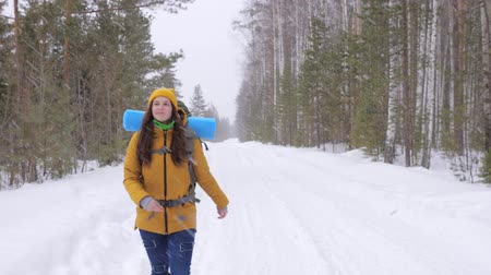 rejoices : Girl tourist in orange winter clothes walking along a winter forest road with a backpack on her shoulders. It is snowing outside. Slow motion. Stock Footage